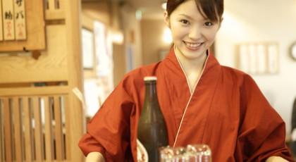 ビールとグラスを運ぶ女性店員
